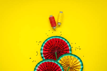 DIY instruction. Step by step tutorial. Making decor for summer birthday party - red and yellow watermelon fan. Craft tools and supplies on yellow background