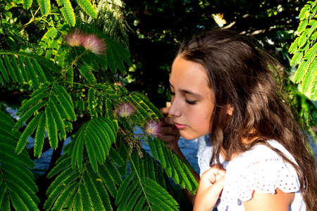 Portrait of a beautiful tanned caucasian cute girl in the tropical greenery. Travel, vacation, warm countries.