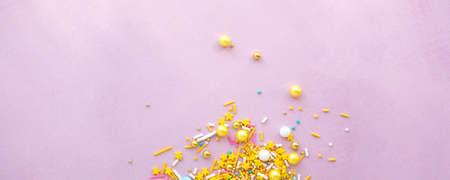 Wide banner Yellow sugar sprinkles grainy on pink background, close-up flat lay with copy space