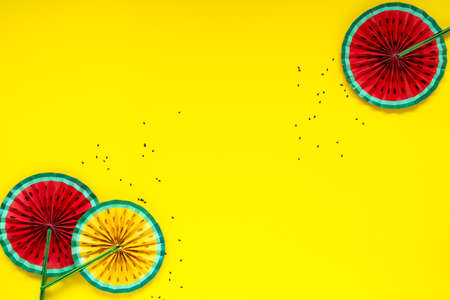 Paper fruit origami watermelon fan decoration. Creative banner with copy space on bright yellow background. Tropics summer