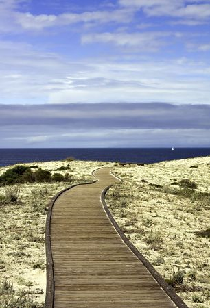Boardwalk over sand dunes with blue sky and clouds in Asilomar State Park on the coast near Pacific Grove, California Stock Photo