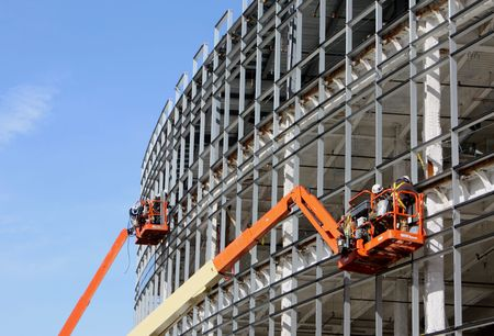 Dźwigów dla pracowników na metalowych WIĄZARY w nowej witrynie budowy przeciw błękitne niebo
