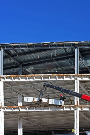 girders: Lift supplying materials to a worker at a new construction site with steel girders and blue sky vertical