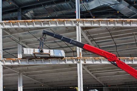 Lift supplying materials to a worker at a new construction site with steel girders and blue sky photo