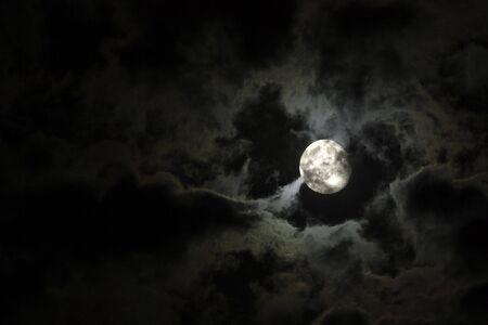 보름달 근접 촬영 및 검은 밤 하늘에 대 한 섬뜩한 흰 구름