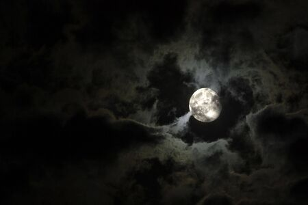 Full moon close-up and eerie white clouds against a black night sky photo