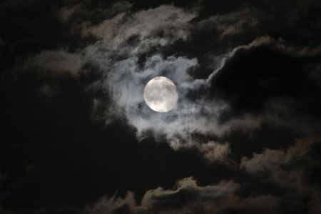 Full moon emerging from eerie white clouds against a black night sky