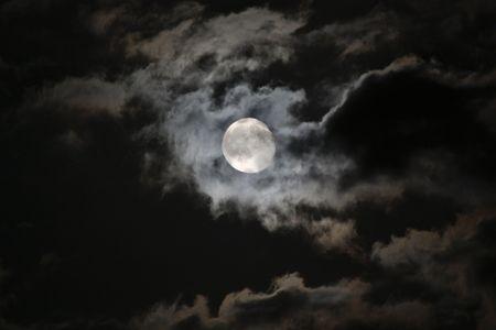 paisaje lunar: Luna llena, surgen inquietantes las nubes blancas contra un cielo de noche negro