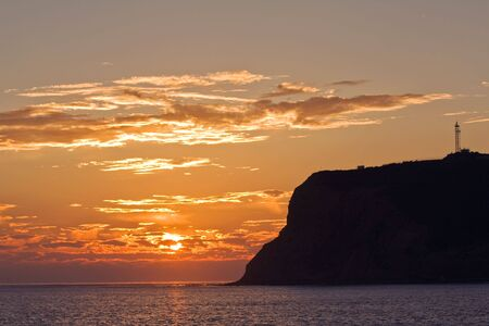 Point Loma silhouetted behind a setting sun and orange sky on the coast of California where San Diego Bay meets the Pacific Ocean Stock Photo