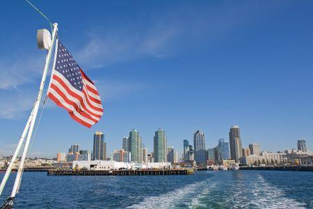 ballena azul: Vista del puerto y horizonte de San Diego, California, desde la taffrail de un buque de ballenas con la bandera de Estados Unidos, cielo azul brillante y las nubes blancas