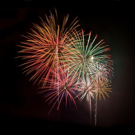 Multicolored fireworks against a black night sky square