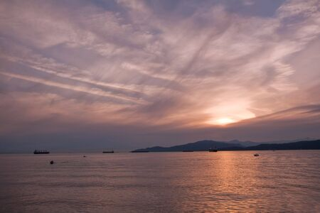 Cargo ships moored in Burrard Inlet off the Strait of Georgia, Vancouver, British Columbia, Canada at sunset photo