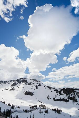 View of snow-covered mountains and dramatic clouds from Whistler Peak in British Columbia, Canada vertical