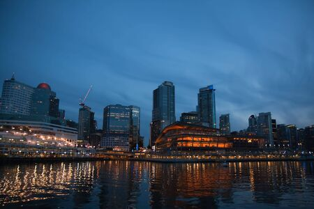 The skyline of Vancouver, British Columbia, Canada, with reflections on the water against a dramatic blue sky at night
