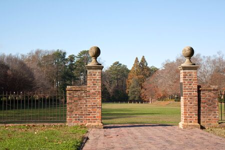 Brick walkway to the sunken gardens on the campus of the College of William and Mary in Virginia with a light blue sky during autumn