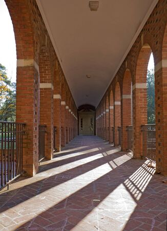 virginia: Arched walkway on the campus of the College of William and Mary in Williamsburg, Virginia, with slanting rays of the morning sun vertical