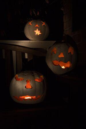 Three lit white jack o'lanterns wait for halloween on a bench at night Stock Photo - 7816498