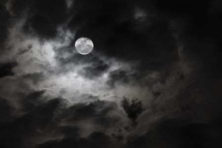 eerie: Spooky full moon and eerie white clouds against a black night sky