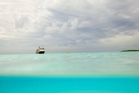 백그라운드에서 식별 할 수없는 유람선과 바하마에있는 해변의 파도 아래 부분적으로 볼 극적인 하늘