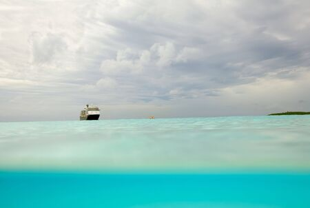 cay: Dramatic sky viewed from partially under the waves of a beach in the Bahamas with an unidentifiable cruise ship in the background Stock Photo
