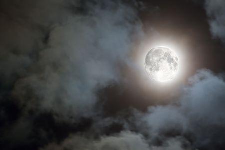 paisaje lunar: Escalofriante de las nubes blancas y una luna llena con un halo contra un cielo negro  Foto de archivo