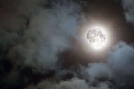Spooky white clouds and a full moon with a halo against a black night sky