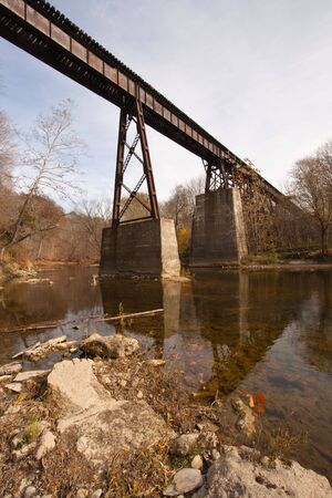 Abandoned railroad bridge over a creek vertical photo