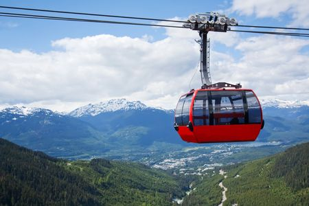 Red car of the aerial tramway connecting two high peaks at Whistler Mountain in British Columbia, Canada with blue sky and white clouds photo