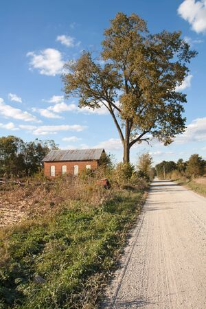 Abandoned on-room schoolhouse on a rural, gravel road in Indiana with a large tree, bright blue sky and clouds vertical photo