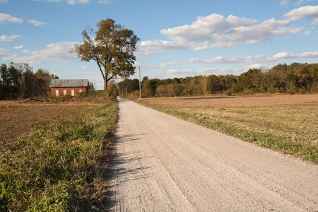 Abandoned on-room schoolhouse on a rural, gravel road in Indiana with a large tree, bright blue sky and clouds Stock Photo - 8199736
