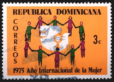 franked: DOMINICAN REPUBLIC - CIRCA 1975: A 3-centavo stamp printed in the Dominican Republic shows a circle of people holding hands to celebrate the International Year of the Woman, circa 1975