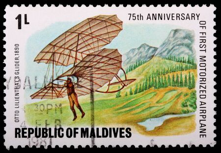 REPUBLIC OF MALDIVES - CIRCA 1981: A 1-laari stamp printed in the Republic of Maldives shows a man in Otto Lillenthals glider, 1890, flying near a mountain range to commemorate the 75th anniversary of the first motorized airplane, circa 1981 Редакционное
