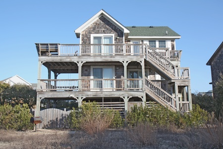 A beach house on the Outer Banks at Nags Head, North Carolina, against a bright blue sky