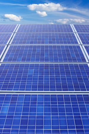 Panels of solar collection cells fade towards a bright blue sky with white clouds vertical photo