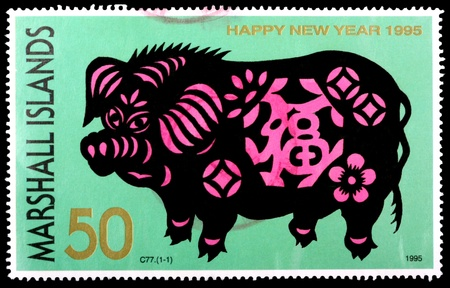 REPUBLIC OF THE MARSHALL ISLANDS - CIRCA 1995: A 50-cent stamp printed in the Republic of the Marshall Islands celebrates happy new year and the Chinese year of the pig, circa 1995 Stock Photo - 10435264