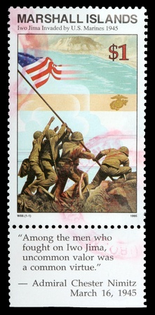 postage stamp: REPUBLIC OF THE MARSHALL ISLANDS - CIRCA 1995: A 1-dollar stamp printed in the Republic of the Marshall Islands shows the raising of the flag when the island of Iwo Jima was invaded by U.S. marines in 1945, circa 1995 Editorial