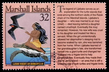 franked: REPUBLIC OF THE MARSHALL ISLANDS - CIRCA 1995: A 32-cent stamp printed in the Republic of the Marshall Islands shows a female islander riding a sea turtle with a frigate bird to tell the story of how Lijebake rescues her granddaughter, circa 1995 Editorial