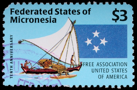 FEDERATED STATES OF MICRONESIA - CIRCA 1996: A 3-dollar stamp printed in the Federated States of Micronesia shows islanders on an outrigger sailing canoe and four stars to commemorate the tenth anniversary of free association with the United States of Ame