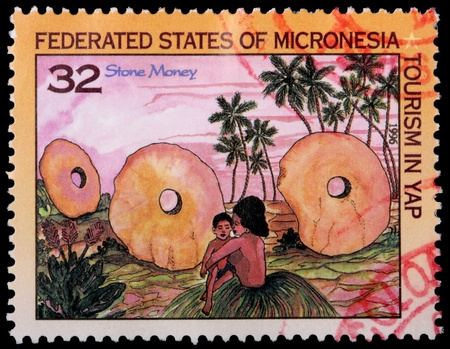 franked: FEDERATED STATES OF MICRONESIA - CIRCA 1996: A 32-cent stamp printed in the Federated States of Micronesia to promote tourism in Yap shows islanders, palm trees and stone money, circa 1996