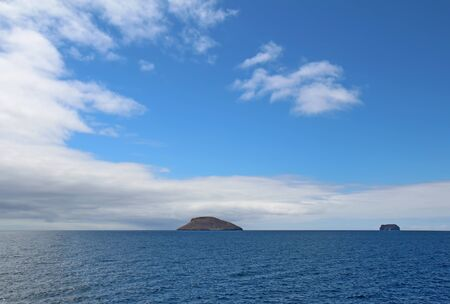 View of the islands Daphne Major and Daphne Minor in the Galapagos National Park, Ecuador, from the water against a bright blue sky and white clouds.  Daphne Major is near the center of the Galapagos island chain and has been the site of intensive study o Stock Photo - 10693541