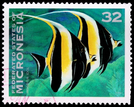 zanclus cornutus: FEDERATED STATES OF MICRONESIA - CIRCA 1996: A 32-cent stamp printed in the Federated States of Micronesia shows a pair of Moorish idol fish (Zanclus cornutus), and coral, circa 1996