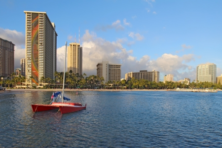 Red catamaran and several hotels along Fort DeRussy beach near Waikiki form a partial skyline of Honolulu, Hawaii