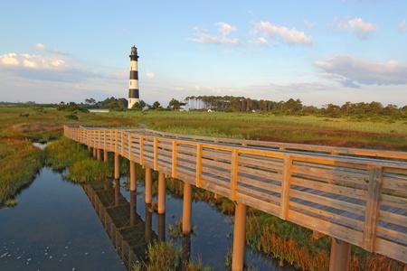青い空と白い雲に対してノースカロライナ州のアウターバンクス ボディー アイランド灯台へ木製の通路、沼地の観点から