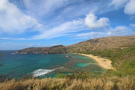 Wide-angle view of Hanauma Bay Nature Preserve near Honolulu, Hawaii with dramatic white clouds and a bright blue sky
