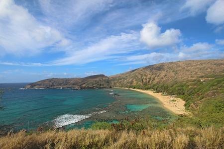 wideangle: Wide-angle view of Hanauma Bay Nature Preserve near Honolulu, Hawaii with dramatic white clouds and a bright blue sky