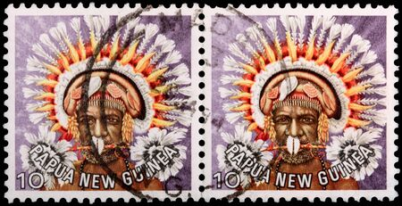 PAPUA NEW GUINEA - CIRCA 1977: Two 10-toea stamps printed in the Independent State of Papua New Guinea shows a man in a feathered headdress from the area near Koiari, circa 1977