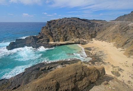 View of the rock walls and sands of Halona Beach Cove near Honolulu on the southeast coast of the Hawaiian island of Oahu. Halona Beach Cove is the location of a famous love scene between Burt Lancaster and Deborah Kerr in the movie, From Here to Eternity