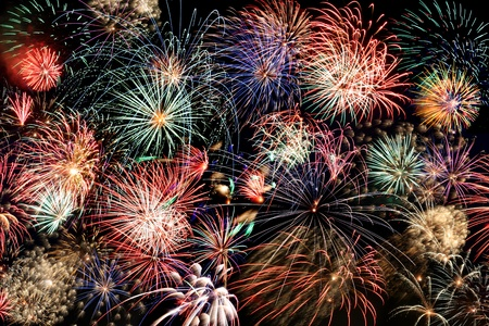fireworks display: Multiple bursts of multicolored fireworks fill the horizontal frame against a black background