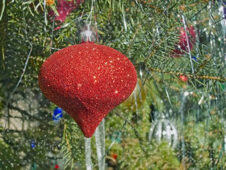 Red Christmas ornament on a spruce tree against a blurred sparkly background photo