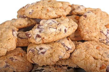 Mound of home-made chocolate and butterscotch chip cookies against a white background